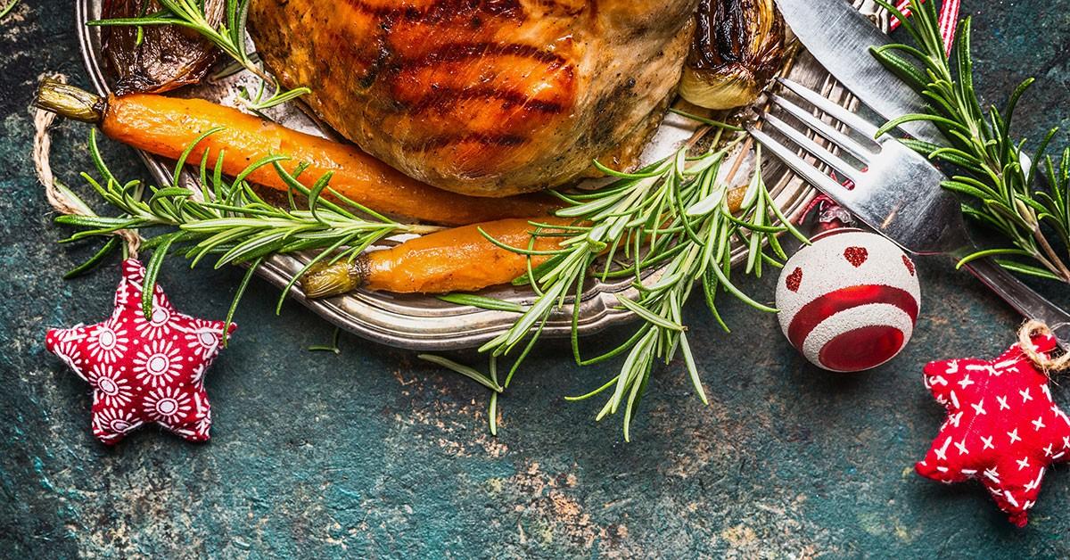 Tallrik med kött och stekta morötter med juldekorationer bredvid