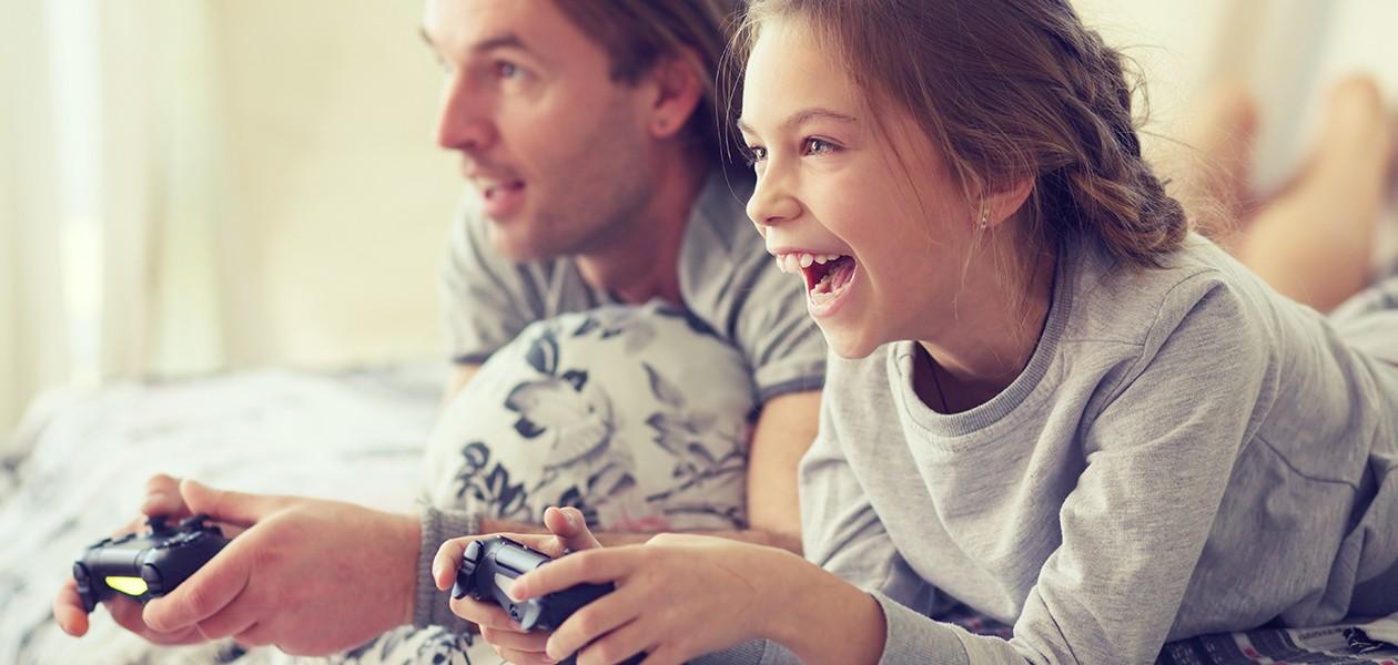 Far, dotter och son som spelar konsolspel framför TV:n medan farfar sover bredvid