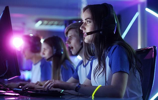 En tjej som gamear med hörlurar på och spelar med sitt lag