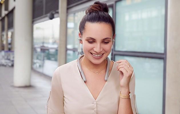Kvinde med trådløse hovedtelefoner i ørerne