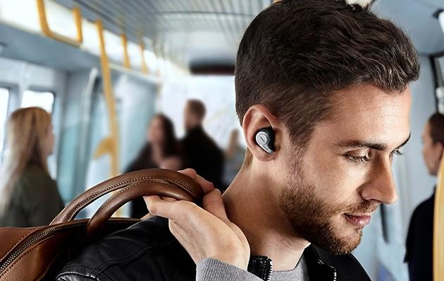 Mand ombord en bus med helt trådløse hovedtelefoner i ørerne