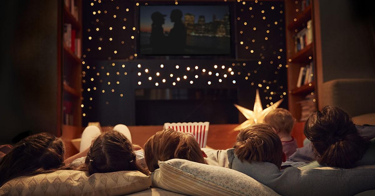 En familj på fyra ligger i soffan framför TV:n