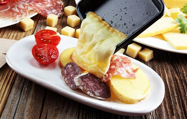 Smält ost som hälls från en raclette över skinka och potatis