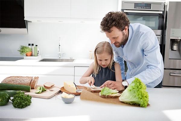 Bild av en kvinna och barn som lagar mat