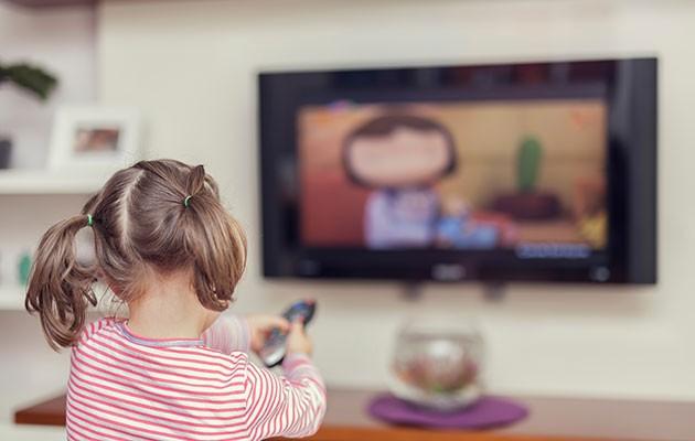 En tjej byter kanal på TV:n i bakgrunden