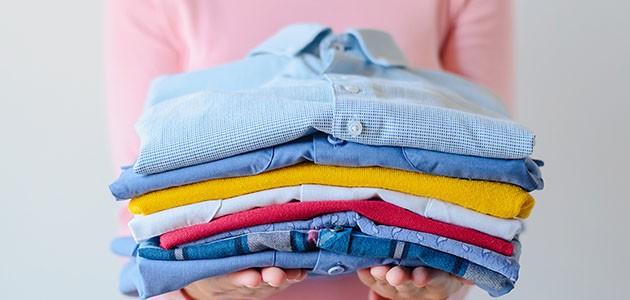 Billede af sammenfoldet tøj i hænderne på en kvinde: Få en rolig og stabil vaskemaskine med et stativ og gummifødder