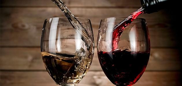 Rød og hvid vin hældes i hvert sit glas ved siden af hinanden på billedet