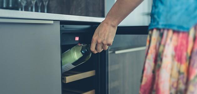 En flaske vin tages ud af en vinkøler
