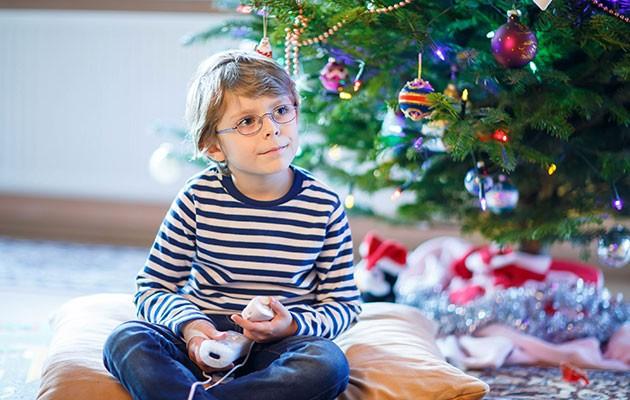 Ett barn med glasögon som spelar Nintendo framför en julgran