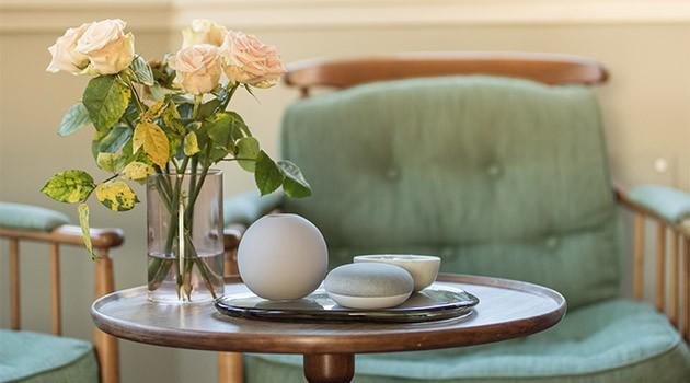 En smarthøyttaler på et sidebord, ved siden av en blomstervase
