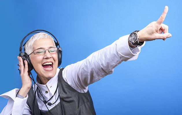 Äldre kvinna med hörlurar som njuter av bra musik och ler