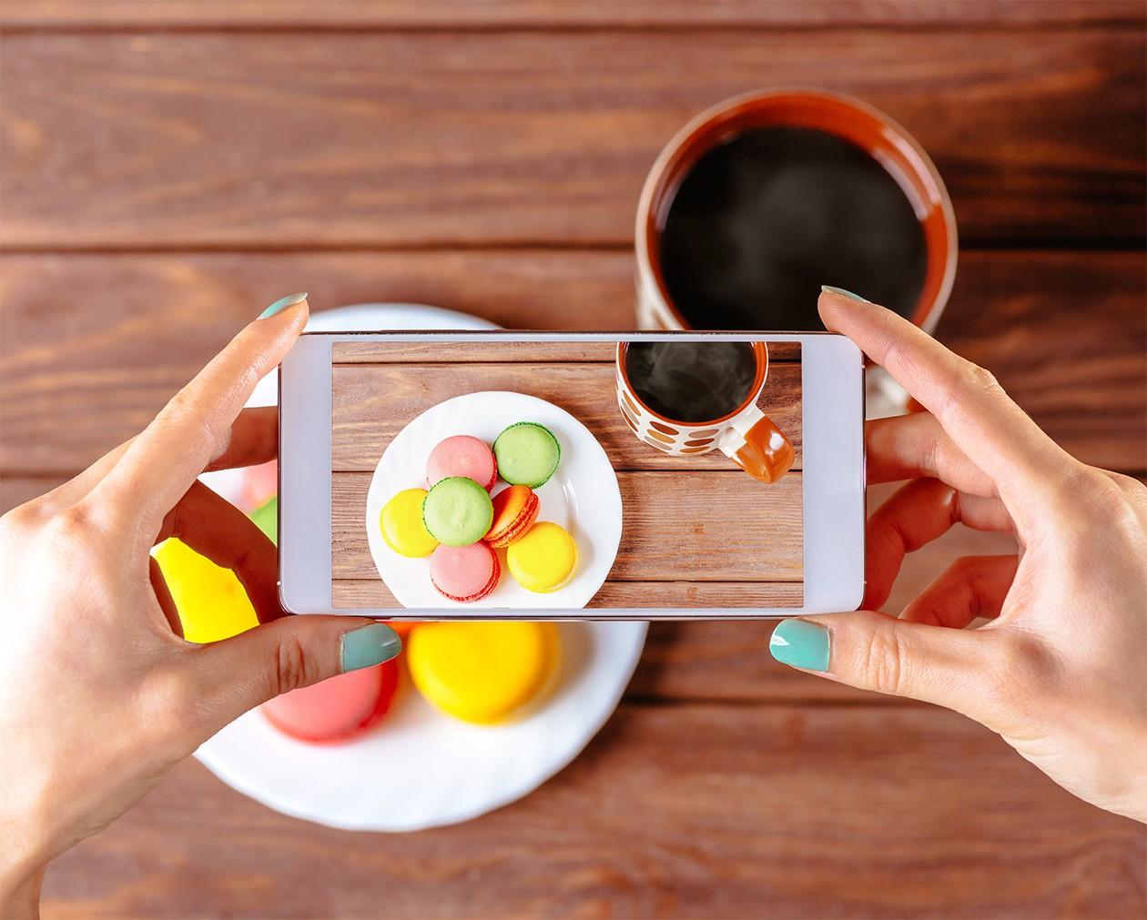 Kvinde tager billede af kager med en smartphone