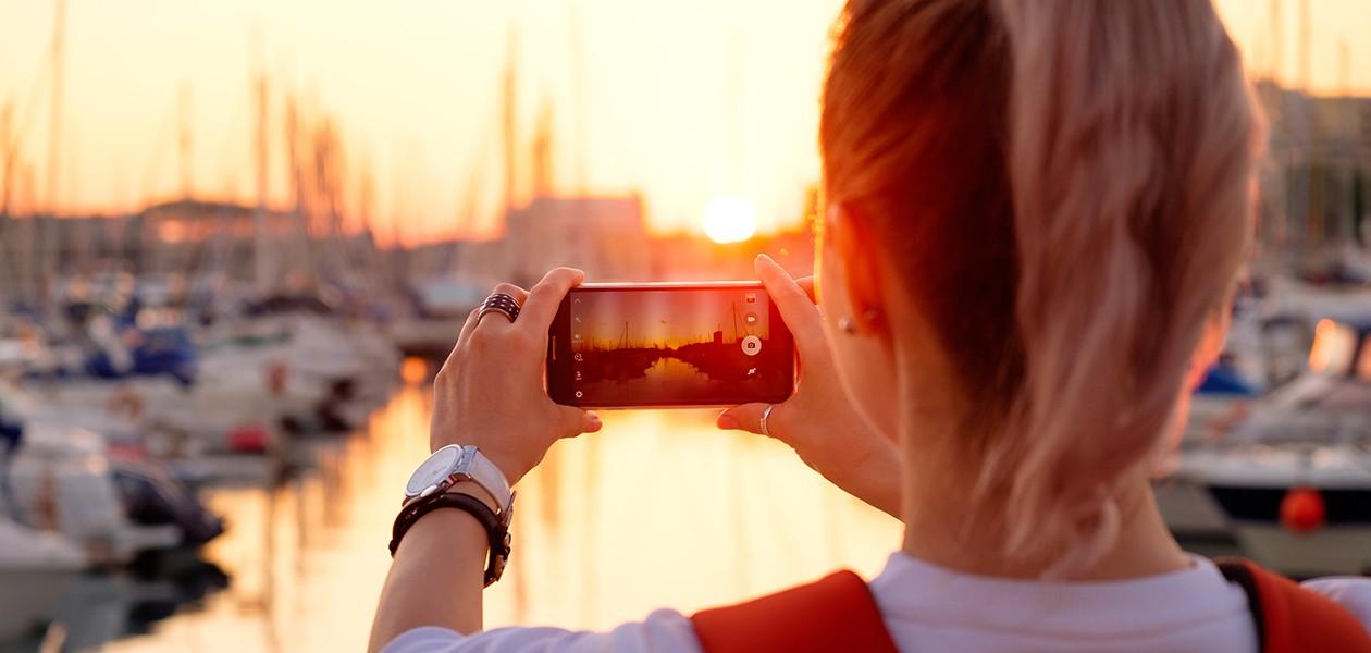 Kvinde tager billede af solnedgangen med en smartphone