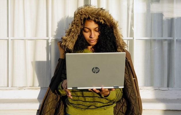 Bild av en ung kvinna med HP Pavilion x360 i handen