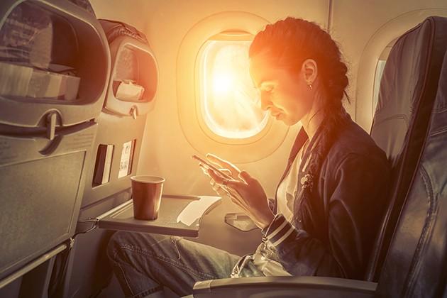 Billede af kvinde på fly med mobiltelefon