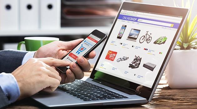 Hender som holder en smarttelefon foran en bærbar PC