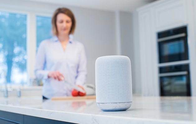 Bild av en smart på en köksbänk, en kvinna i bakgrunden