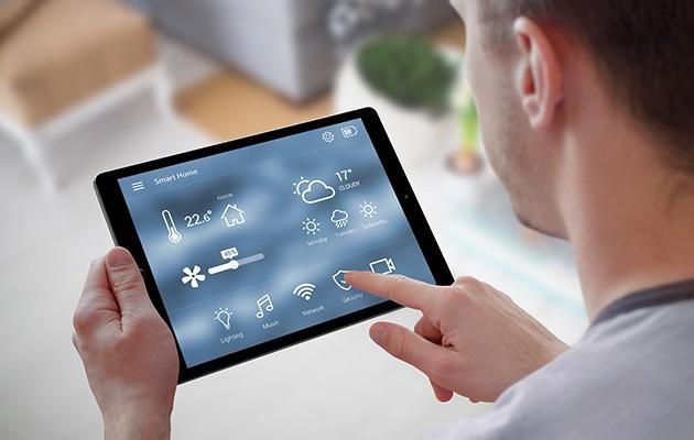 En man som håller i en surfplatta med smart home-symboler på skärmen
