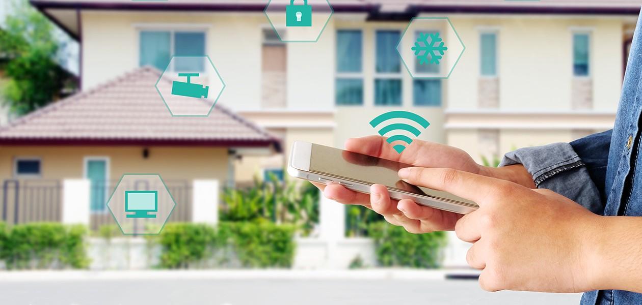 Händer som håller en mobil med ett hus i bakgrunden och symboler på skärmen