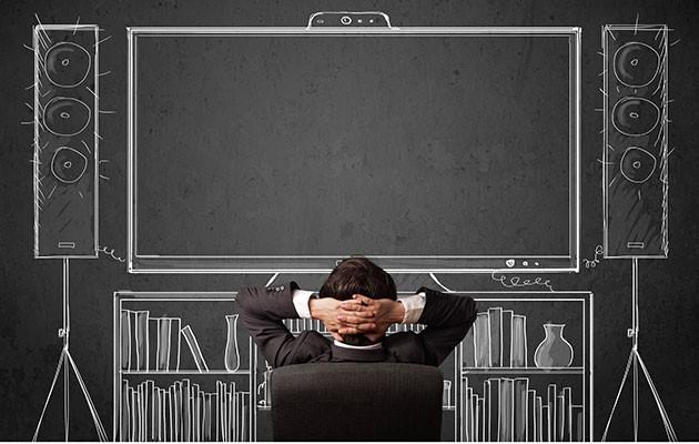 En man sitter framför en TV och ljudanläggning