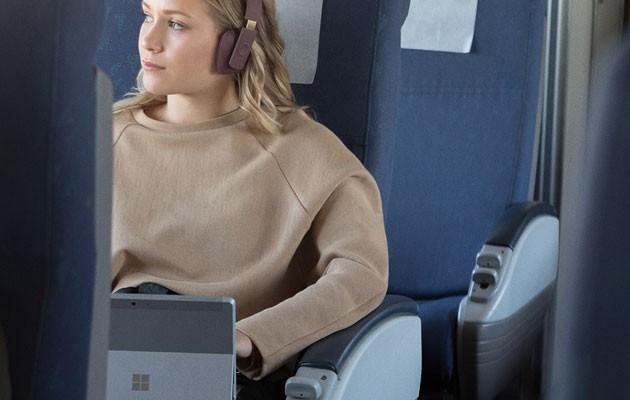 Bild av en unga kvinna på ett tåg med Surface Go i handen