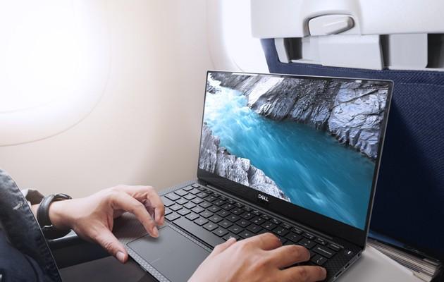 Ung mann i et flysete med PC-en XPS 13 foran seg